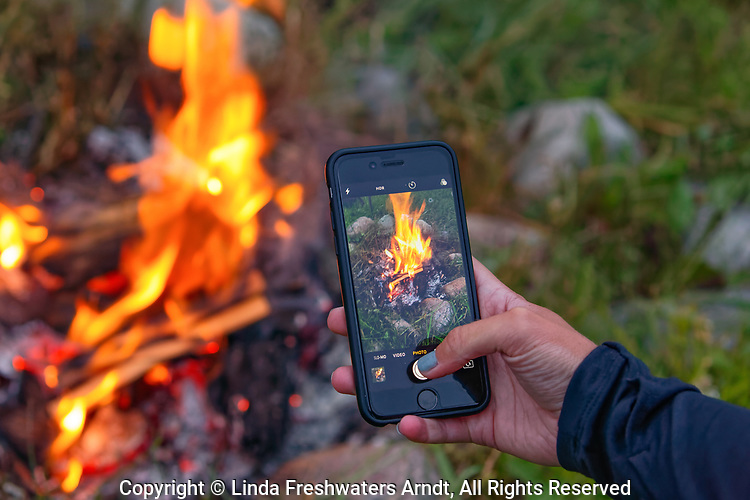Young woman taking a picture of the campfire to share with friends.
