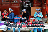 Vendors the ethnic Bouyei Tribe sell traditional shoes at Wangmo County in China's southwestern Guizhou Province, April 2019.