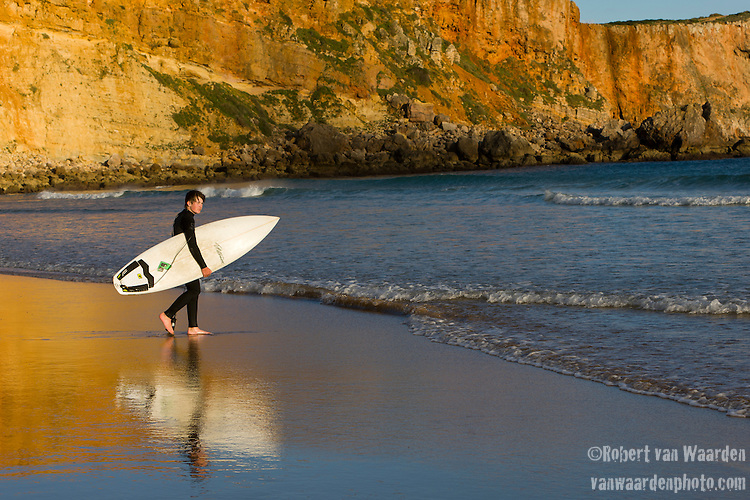 A young surfer enjoys the waves while in the background the yellow red cliffs of Sagres reflect in the water