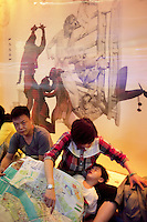 China. Shanghai. World Expo. Expo 2010 Shanghai China.  China Pavilion. A family, all chinese tourists, seats and rests on the ground. The child is asleep and leans his head on his mother's leg. The mother is busy organising with her husband the day and looks at the expo map. 25.06.10 © 2010 Didier Ruef