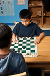 Afterschool chess program for elementary students graduates of Headstart program two boys playing one boy holding chess piece as he decides on move looking at opponent for his reaction