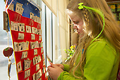 MR / Schenectady, NY. Zoller Elementary School (urban public school). Kindergarten inclusion classroom. Student (girl, 5) selecting activity from pocket chart for learning center time. MR: Deg9. ID: AM-gKw. © Ellen B. Senisi.