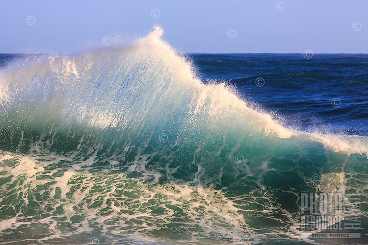 Light shines on a wall of water, illuminating the wave like blown glass in background of deep blue, Lumaha'i Beach, northern Kaua'i..