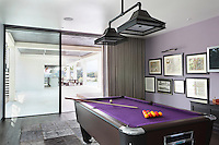 A mauve games room with a matching purple felt pool table