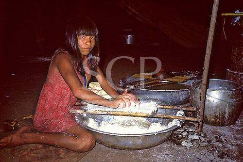 Pavuru Village, Brazil. Village woman grating manioc (Manihot esculenta, mandioca, cassava).