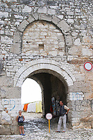 The entrance to the old city, arched gate in the stone wall, young boy, stop sign and a man ticket controller standing guard. Berat upper citadel old walled city. Albania, Balkan, Europe.