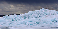 A panoramic view of a giant pile of Lake Superior ice stacked with a spring rain showers in the distance. Marquette, MI