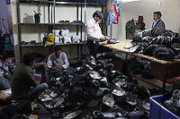 Factory workers sit amongst large piles of leather shoes in a workshop in the Jajmau area of Kanpur. Many of the city's leather products are destined for western markets.