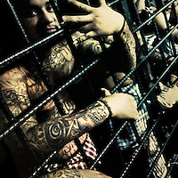 A member of the 18th Street Gang (M-18), showing the hand sign of his gang, stands behind the bars in a detention cell in San Salvador, El Salvador, 19 February 2014.