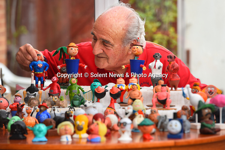 Pictured:  Tony Amatruda at his home in Basingstoke, Hants.<br /> <br /> Golf fanatic Tony Amatruda has stunned friends by turning hundreds of old balls into models of famous characters including Homer Simpson, E.T. and Donald Trump.  When he returns from a round, 82-year-old great grandfather spends hours moulding tiny bits of clay onto his old balls before carefully drying them with a hairdryer and painting them.<br /> <br /> He even has a series of handmade tools he uses to add fine details and the painstaking process can take days.  Now his conservatory and three shelves of the glass cabinet in his sitting room are stacked with around 150 of the comical designs which include Miss Piggy, Yoda and a host of different animals.  SEE OUR COPY FOR DETAILS.<br /> <br /> © Roger Arbon/Solent News & Photo Agency<br /> UK +44 (0) 2380 458800