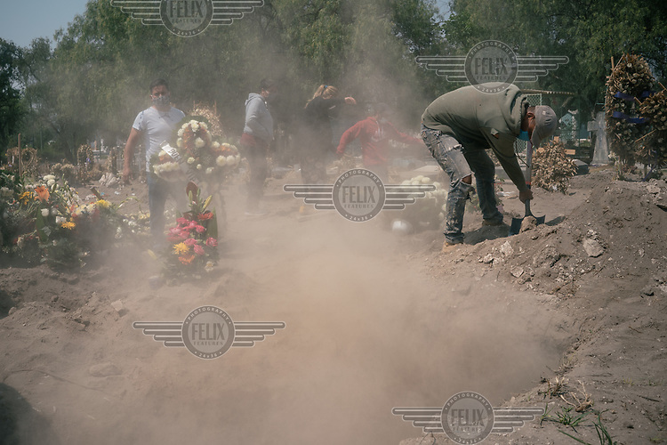 A worker at the Lorenzo Tezonco public cemetery in Iztapalapa fills in a grave as family members observe from a few feet away. The services are performed quickly as there is often a line of funeral vans waiting with new bodies to bury.