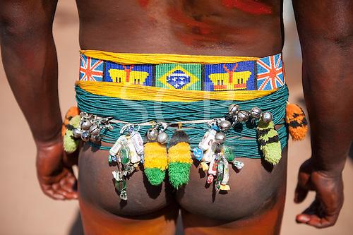Xingu Indigenous Park, Mato Grosso, Brazil. Aldeia Matipu. Beadwork belt with Union Jack, Brazilian flag and headdress motifs. Floresta sweets and bells.