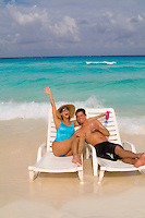 Young Hispanic couple on lounge chairs on the beaches of Cancun Mexico