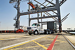 """""""Green Truck"""" under large shipping cranes at the Port of Long Beach."""