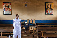 """Nigeria. Enugu State. Awhun. Saint Luke's Catholic Parish. An old Igbo man dressed with white clothes and wearing a catholic pectoral cross on his neck stands in the church before the funeral mass in honor of Reverend Father Clement Rapuluchukwu Ugwu, killed by burglars in his house on March 13th 2019. A pectoral cross or pectorale is a cross that is worn on the chest, usually suspended from the neck by a cord or chain. Two drawings from Jesus Christ and the sacred heart are hanged in frames on the wall. The one on the left is accompanied by words from psalm 23 of the Book of Psalms, generally known by its first verse, """"The Lord is my Shepherd"""".  In between both religious portraits of Jesus Christ, a written sign is english: Off your phones. 11.07.19 © 2019 Didier Ruef"""