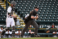 Home plate umpire Nate Tomlinson gets in position to make a call as catcher Chris Stewart looks on during a game between the Palm Beach Cardinals and Bradenton Marauders on April 8, 2014 at McKechnie Field in Bradenton, Florida.  Bradenton defeated Palm Beach 4-3.  (Mike Janes/Four Seam Images)