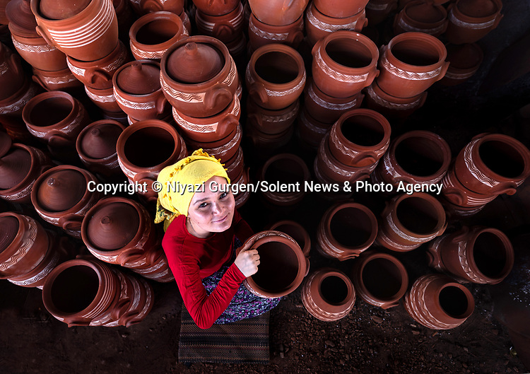 A woman arranges handmade clay pottery after being taken out of the furnace. 