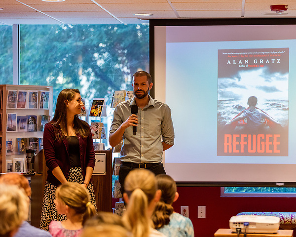 """July 26, 2017. Raleigh, North Carolina.<br /> <br /> Rachael Borowy and Ryan Smith of the US Committee for Refugees and Immigrants spoke to the crowd before Alan Gratz's author's talk. <br /> <br /> Author Alan Gratz spoke about and signed his new book """"Refugee"""" at Quail Ridge Books. The young adult fiction novel contrasts the stories of three refugees from different time periods, a Jewish boy in 1930's Germany , a Cuban girl in 1994 and a Syrian boy in 2015."""