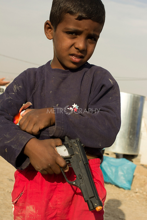 DOMIZ, IRAQ: A Syrian refugee plays with a plastic gun in the Domiz refugee camp in the Kurdish region of northern Iraq...The semi-autonomous region of Iraqi Kurdistan has accepted around 60,000 refugees from war-torn Syria. Around 20,000 refugees live in the Domiz camp which sits 60 km from the Iraq-Syria border...Photo by Younes Mohammad/Metrography