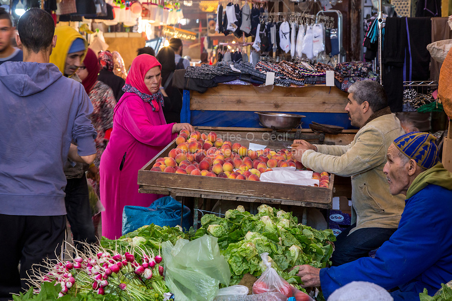 Fes, Morocco.  Woman Examining Peaches in the Tala'a Kabira Street Market, Fes El-Bali.