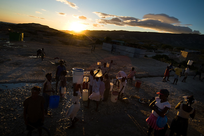 """people carrying water they just got out of the tabs at sheltercamp """"hanna de praville"""" in Gonaives."""