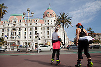 Rollerbladers on the Promenade des Anglais pause to look at the Negresco Hotel, Nice, France, 28 April 2012.