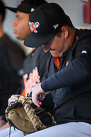 Zach Booker (52) of the Norfolk Tides repairs a broken lace on a catchers mitt during the game against the Charlotte Knights at BB&T BallPark on July 17, 2015 in Charlotte, North Carolina.  The Knights defeated the Tides 5-4.  (Brian Westerholt/Four Seam Images)