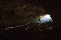 Caver at entrance to karstic cave in the Dinaric Alps, Slovenia. April.