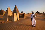 Nubian guide in front of an ancient pyramid (Mut temple?) on the Meroe Site.<br /> More than fifty ancient pyramids and royal tombs rise out of the desert sands at Meroe.<br /> Black Pharaohs Sudan