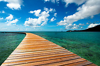 Beautiful, curved wooden pier on the turquoise sea under a blue sky, at Saintes-Anne, in French Martinique Island, Caribbean Windward Islands