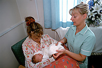 Midwife attending to new born baby who is being held by her mother. This image may only be used to portray the subject in a positive manner..©shoutpictures.com..john@shoutpictures.com