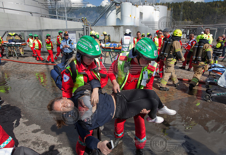 """Paramedics tend to """"victims"""" and firefighters put out a fire in an oil facility. HarbourEx15, a field training exercise with scenarios connected to operations in the harbor April 27th – 29th 2015.<br /> <br /> The scenario of the exercise is a major accident on Sydhavna /Sjursjøya area of Oslo, and will involve rescue and emergency response agencies from tactical to strategic level. (photo: Fredrik Naumann/Felix Features)"""