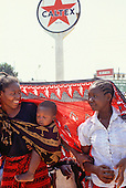 Tabora, Tanzania. Two women and a baby sheltering under a cotton cloth with Caltex  sign.