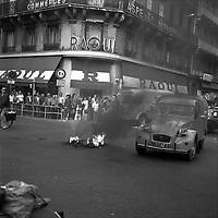"""Carrefour de l'avenue d'Alsace-Lorraine et de la rue Lafayette. 5 septembre 1975. Au 1er plan feu et fumée au milieu de la route (pneus), une voiture et une mobylette passe à côté ; en arrière-plan foule sur le trottoir à l'angle de la rue regarde la scène, façades, commerce """"Raoul"""". Cliché pris lors d'une manifestation contre le Général Franco."""