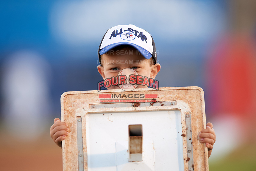 A young fan helps the ground screw change bases during a Dunedin Blue Jays game against the Clearwater Threshers on April 8, 2017 at Florida Auto Exchange Stadium in Dunedin, Florida.  Dunedin defeated Clearwater 12-6.  (Mike Janes/Four Seam Images)