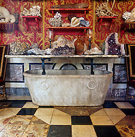 In the main living room an original and quirky console table has been constructed from a marble bath and is used to display an extensive collection of coral and semi-precious stones in their raw state