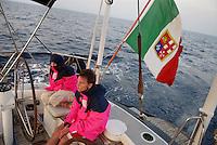 - leisure sailing boat in navigation on the Southern Mediterranean sea, two young people to the rudder wheel ....- barca a vela da diporto in navigazione nel mare Mediterraneo Meridionale, due giovani al timone