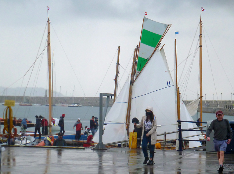 There are at least two topsail-toting Howth 17s seen here arriving into the NYC's mini marina, in a hurry as the rain begins in earnest, yet somehow they stop in the nick of time. Note how the two masts of the DB21s beyond are carrying classically-hoisted DBSC burgees. Photo: W M Nixon