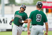 Chuckie Jones (20) of the Augusta GreenJackets is greeted by third base coach Mike Goff (9) as he rounds the bases after hitting a 2-run home run against the Greensboro Grasshoppers at NewBridge Bank Park on August 11, 2013 in Greensboro, North Carolina.  The GreenJackets defeated the Grasshoppers 6-5 in game one of a double-header.  (Brian Westerholt/Four Seam Images)