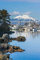 Commercial fishing boats in New Thomsen harbor, Sitka, Alaska. Inactive volcano, Mount Edgecumbe on Kruzof Island in the distance.