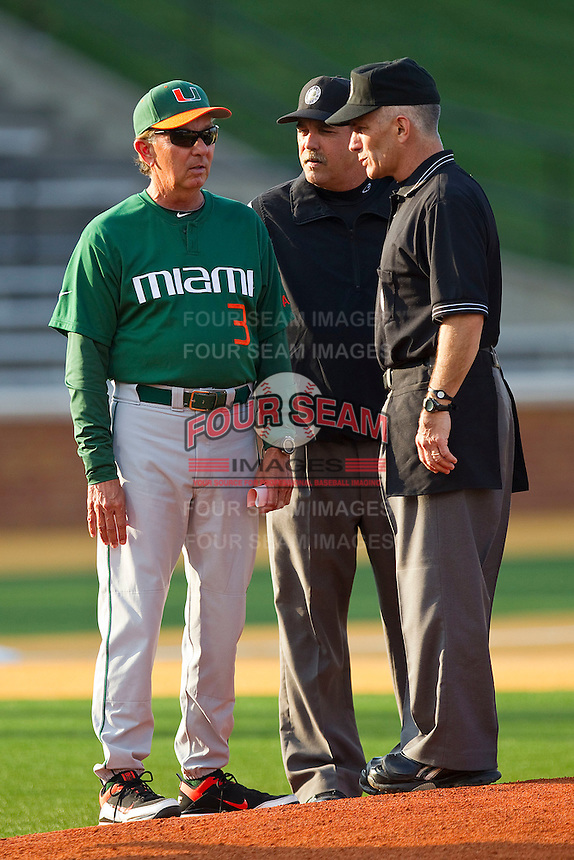 """Miami Hurricanes head coach Jim Morris #3 meets with umpires prior to the game against the Wake Forest Demon Deacons at Gene Hooks Field on March 18, 2011 in Winston-Salem, North Carolina.  Morris felt that the mound was too high, but it was found to be the regulation 10"""" above home plate.  Photo by Brian Westerholt / Four Seam Images"""