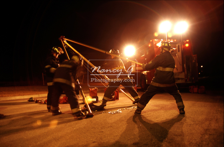 Confined Space Entry training to raise a support Tri-pod at night by the Fire Department