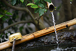 Chozubachi, water cleansing ritual basin with a bamboo spout and a dipper, depicting Japanese Wabi-Sabi aesthetics philosophy that finds beauty in natural aging and imperfection. Byodoin Buddhist temple in Uji, Kyoto Prefecture, Japan 2017 Image © MaximImages, License at https://www.maximimages.com
