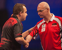 21.12.2014.  London, England.  William Hill World Darts Championship.  Kim Huybrechts (18) [BEL] shakes hands with Mickey Mansell [NIR] before their  match.