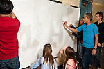 High school students working on poster penciling in projected image they made topic is world peace and racial harmony.