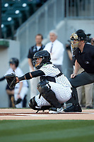Charlotte Knights catcher Alfredo Gonzalez (21) warms up his pitcher prior to the game against the Scranton/Wilkes-Barre RailRiders as home plate umpire Richard Riley looks on at BB&T BallPark on April 12, 2018 in Charlotte, North Carolina.  The RailRiders defeated the Knights 11-1.  (Brian Westerholt/Four Seam Images)