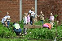 Schulgarten, Anlage eines Schmetterlingsgarten, Garten der Grundschule Nusse wird als Projektarbeit von einer 1. Klasse gestaltet, Kinder und Mutter bei der Beetpflege, Gartenarbeit