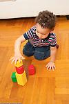 Toddler boy age 18 months at home playing making stack of three blocks