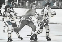 Mike Pelyk (4) and Jim McKenny (18) of Maple Leafs attempt to put squeeze on Atlanta Flames' Curt Bennett in Saturday night's National Hockey League game at the Gardens. Leafs rallied to overcome two-goal deficit in third period to claim 3-3 tie.