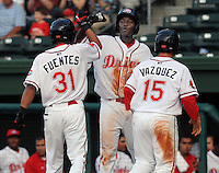 Outfielder Vladimir Frias (29), center, high-fives outfielder Reymond Fuentes (31) after both scored against the Augusta GreenJackets in a game on May 20, 2010, at Fluor Field at the West End in Greenville, S.C. First baseman Christian Vazquez (15) is at right.  Photo by: Tom Priddy/Four Seam Images